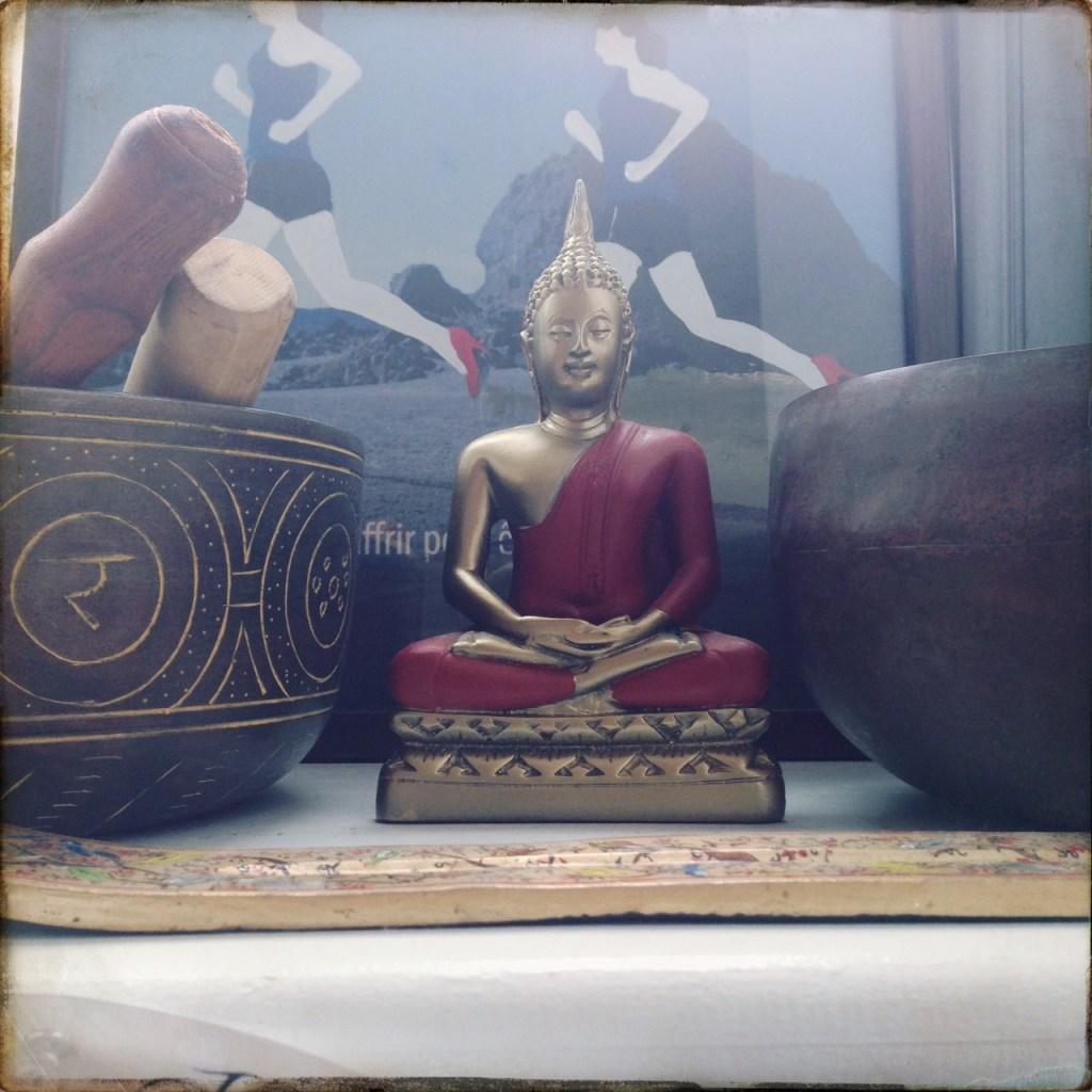 Buddha sitting, so very peacefully, between three singing bowls.