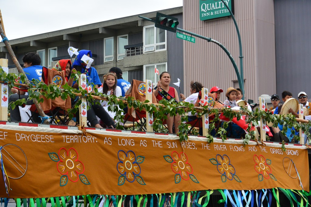 "This image shows a Canada Day float. The people on the float are wearing indigenous regalia and waving Canada flags. The banner on the float reads ""Drygeese Territory"" and ""As Long as this Land Shall Last"". Flowers on the banner are made to resemble traditional beadwork."