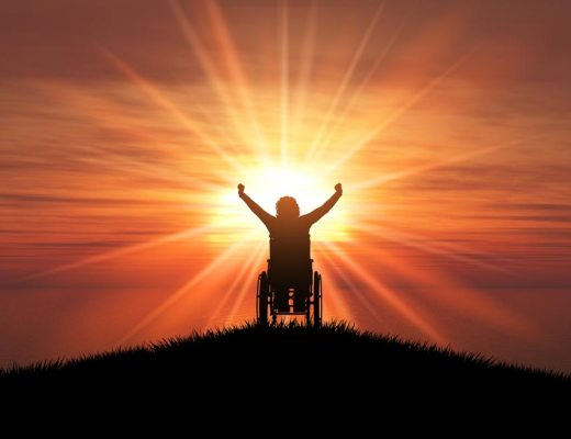 Inspiration porn! Silhouette of person in wheelchair with hands raised in triumph. And a background of an orange sun.