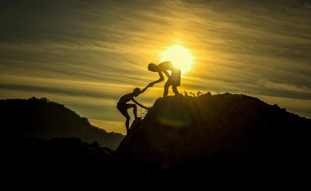 "Silhouettes of two people at the top of a mountain, one helping pull the other up. ""Asking for help up a Mountain"" as a metaphor for depression."