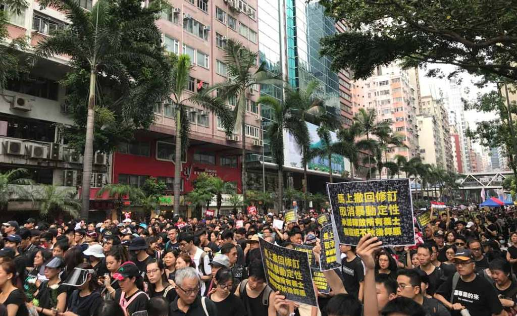 Hong Kong people filling up the streets in freedom protest; wearing black and holding signs.
