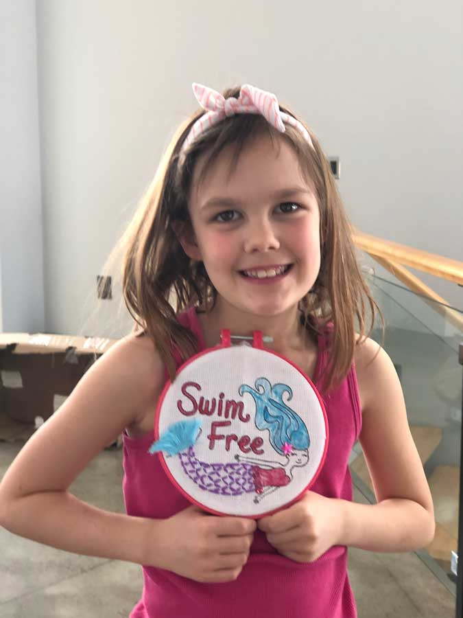Co-worker holding swim free embroidery in hoop