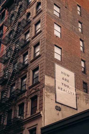 """How are you really?"" sign on the side of a building"