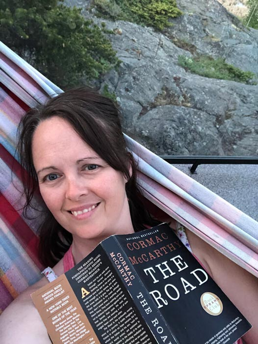 Amber laying in a hammock with a book in daylight because she lives in the North
