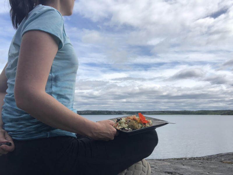 Amber sitting by the lake with her salad and earbuds
