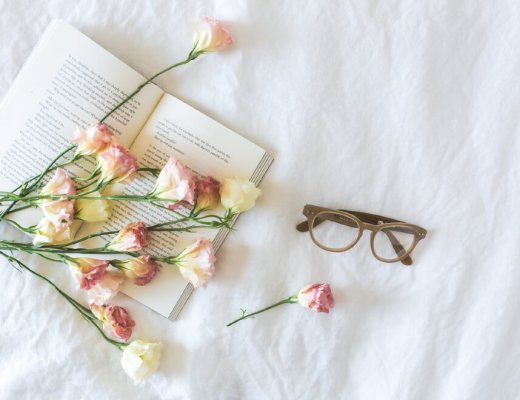 A steamy romance book on a bed, covered in flowers