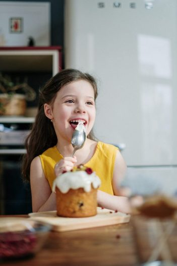 Young birthday girl in front of cake, licking a spoon