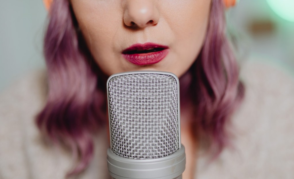 Woman speaking into mic for podcast on disability