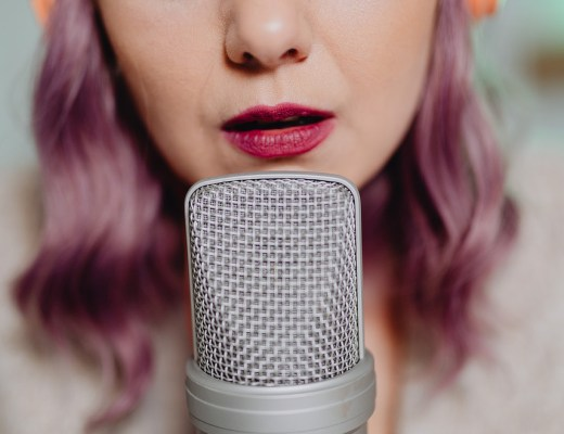 Woman speaking into mic for postcast Not Enough Air Time