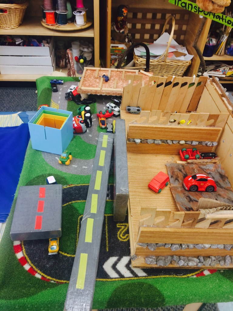 This is co-created road/race track. The children and staff created this using an old dresser drawer and a variety of recycled materials.