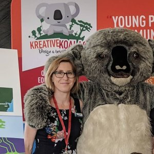 Someone in a large koala suit, with their arm around a female teacher