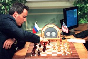 A man makes a chess move, against a computer monitor, his opponent