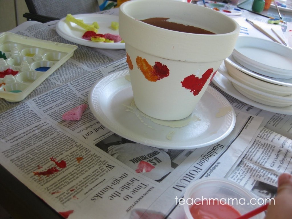 white flower pot with red hearts painted on