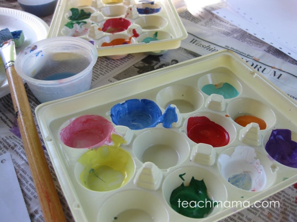 palate of colors near water and paint brush