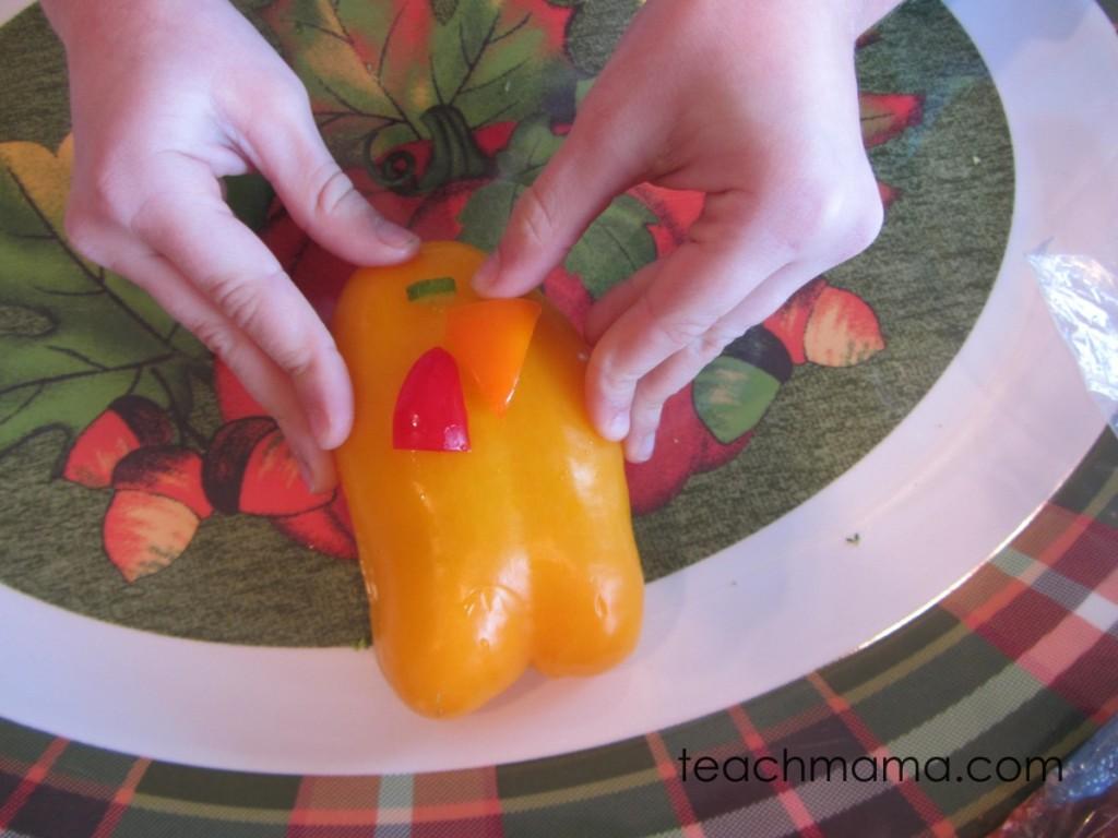 girl's hands adding orange pepper beak to yellow pepper body