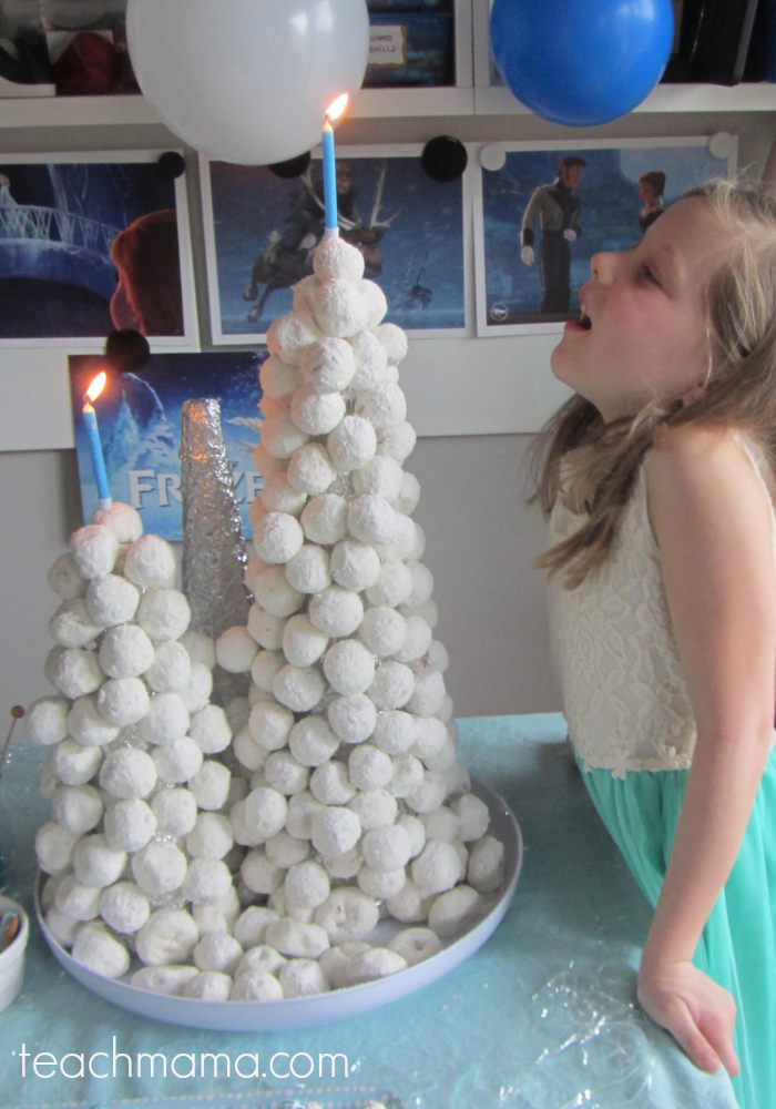 girl blowing out candle in snowball tower cake