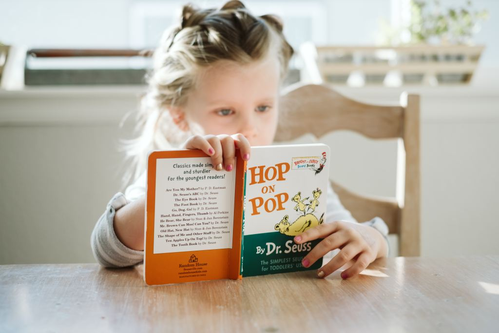 A little girl sitting at a table reading Hop on Pop by Dr. Seuss