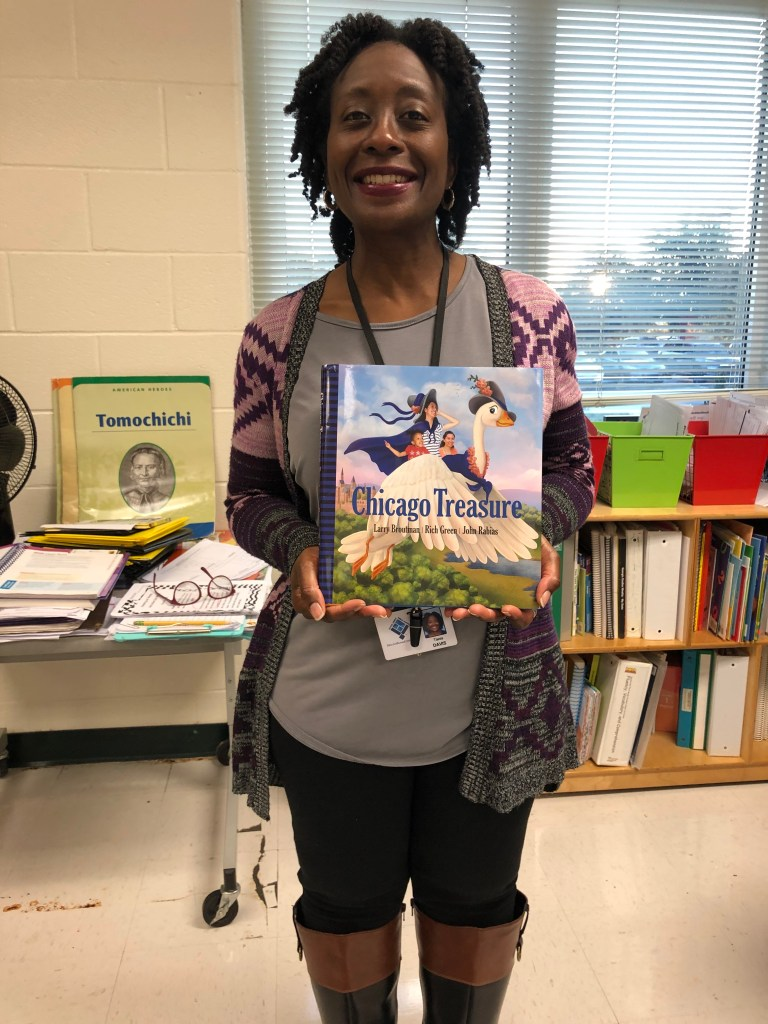 An image of Tania N. Davis standing inside of a classroom.  A smiling, African-American woman dressed in a grey blouse and a tribal-inspired pink, purple, grey, and navy blue cardigan.  I am holding a hardback copy of the book Chicago Treasure.
