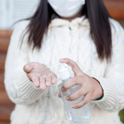An image of a young girl wearing a mask and squeezing hand sanitizer into her hand.