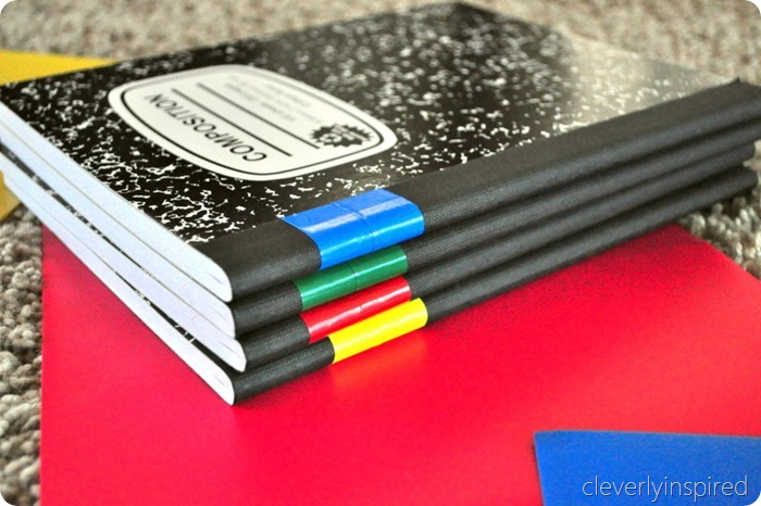 An image of 4 Composition Notebooks sitting on a red piece of paper that is laid on a carpet.  Each book is black in color.  There is a piece of colored Duct Tape on each book- one blue, one green, one red, and one yellow piece of tape.