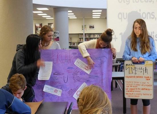 Students present on theme development in To Kill a Mockingbird