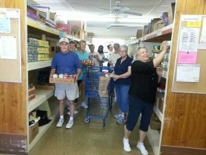 Wednesday volunteers loading up a cart for a client family, plus restocking the shelves.  It can get hectic at times.