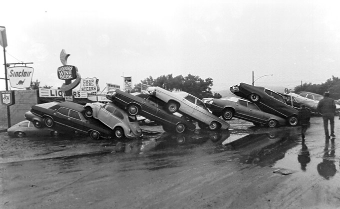 vintage snap of head scratching car pileup at Sinclair gas station