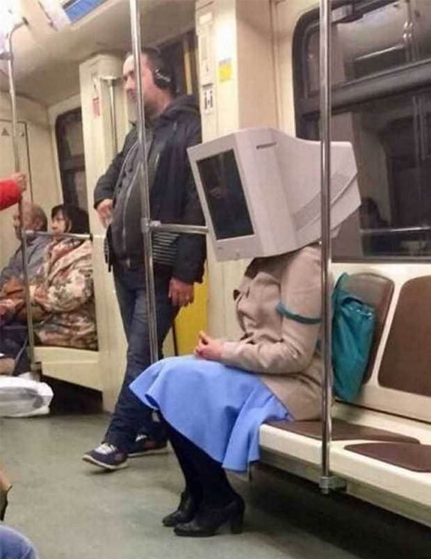 Time to reboot my need to ride public transportation. Woman on subway with computer monitor head.