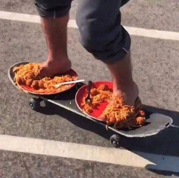 That's gotta feel good! barefooted skateboarder on 2 plates of spaghetti and meatballs