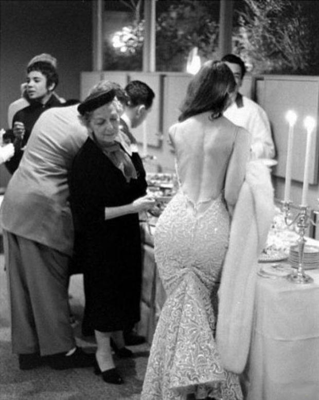 Vintage pic, cocktail party, old woman checking out woman in gown's butt