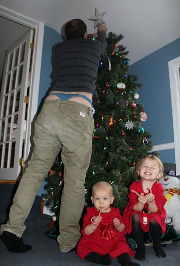 Looks like dad spoiled his Christmas surprise for momma! ~ FunniestFamily Christmas Photos ~ man placing star on Christmas tree with ting underwear hanging out