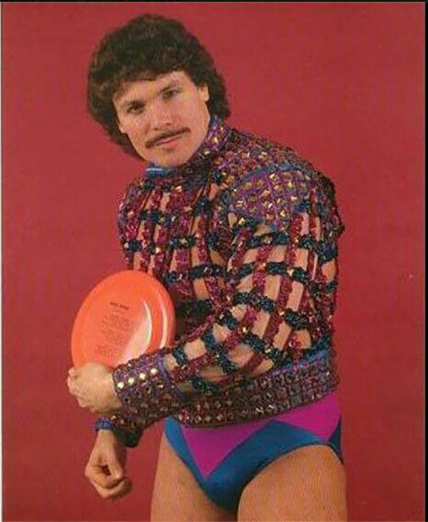 Creepy 1970s stock photo of man in gladiator sweater, speedo and holding a frisbee
