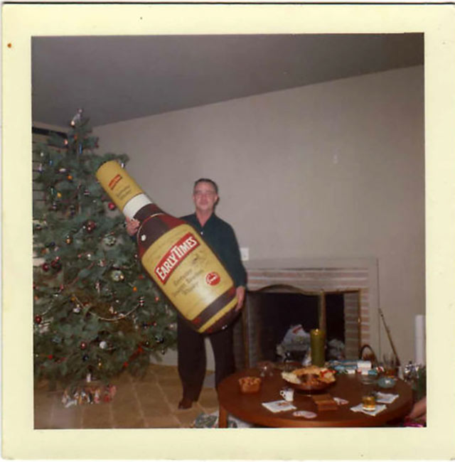 Well, we know who got lit up this Christmas... ~ Funny Family Christmas Photos ~ man holding giant Early Times Whiskey bottle