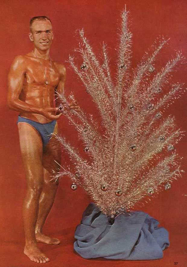 As Tony believes, apply a liberal amount of oil will keep the aluminum tree from rusting. ~ Awkward Funny Family Christmas Photos ~ old vintage Christmas card man in speedo all oiled up next to an aluminum tree