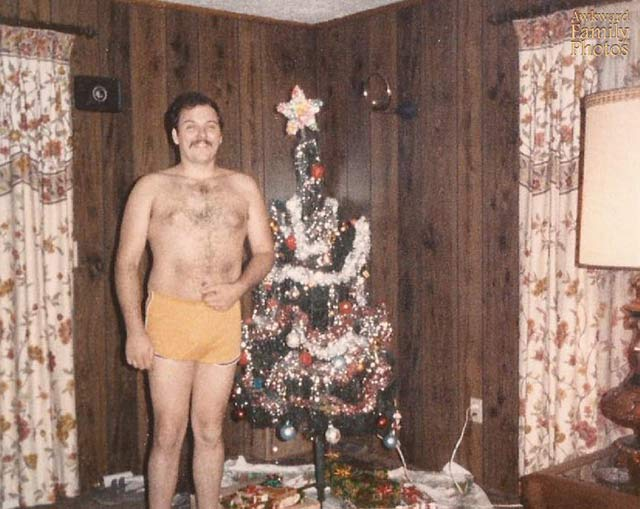Heatin' up the Holidays with cousin Merle. ~ Funny Family Christmas Photos ~ barchesteqd man in short posing next to tree