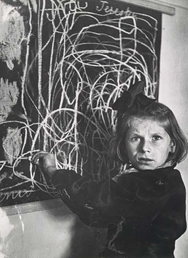 """Her name was Tereska and she grew up in a concentration camp. Seen here in 1948 living in a residence for disturbed children in Poland. She was asked to draw a picture of """"home."""""""