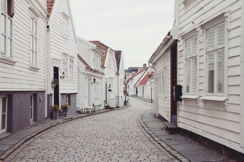 empty roadway in between houses at daytime