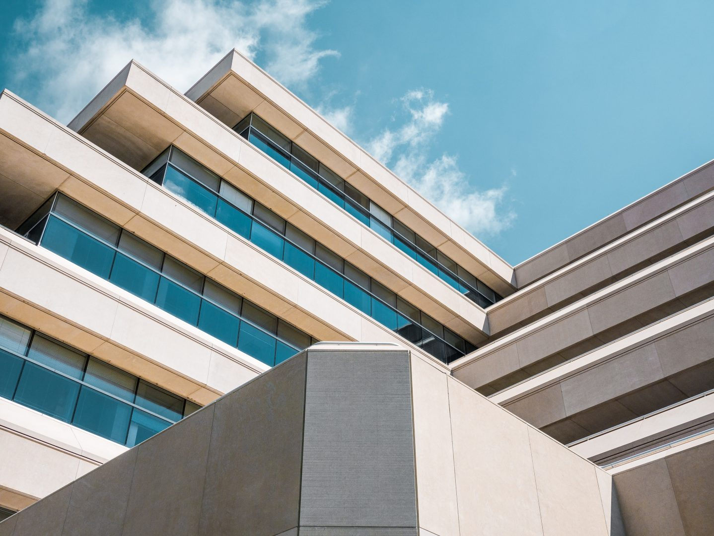 low angle photo of beige concrete building under cloudy sky
