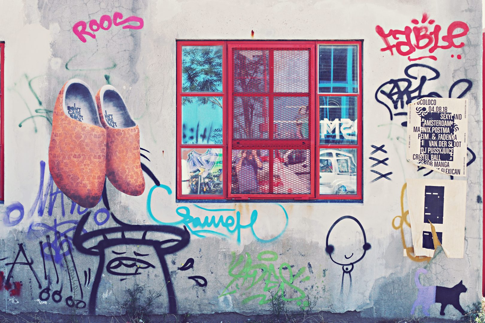 gray wall with red window and graffiti
