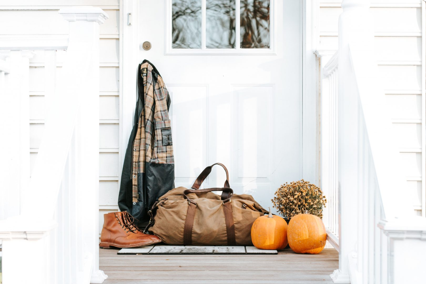 brown duffel bag in front of door