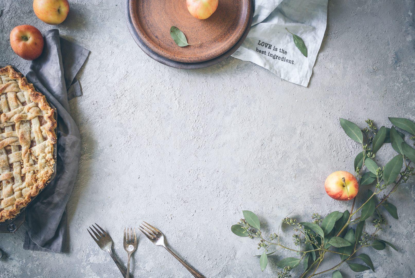 three stainless steel forks near apple