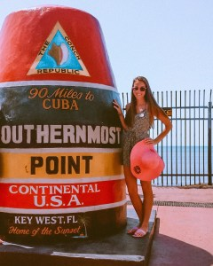 girl standing at the southernmost point marker holding a big pink sun hat