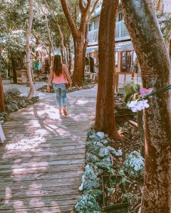 girl walking down a wooden path through shops at rainbarrel village in the florida keys