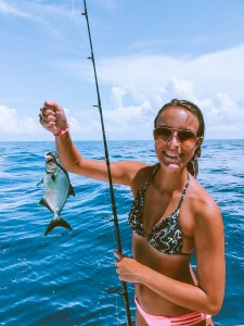 girl holding a small fish on a line with the ocean in the background in the florida keys
