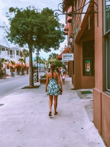 girl wearing a tropical sundress walking down duval street in Key West during the day