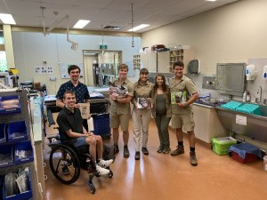 Daniel and William with Irwin family inside veterinarian operating theatre presenting books