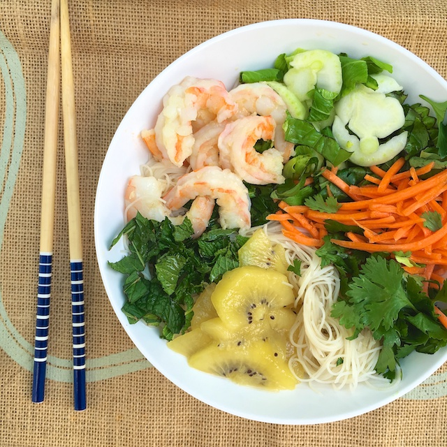 Perfect for hot weather, this gluten-free shrimp noodle salad has a surprising ingredient: SunGold Kiwifruit! [sponsored]