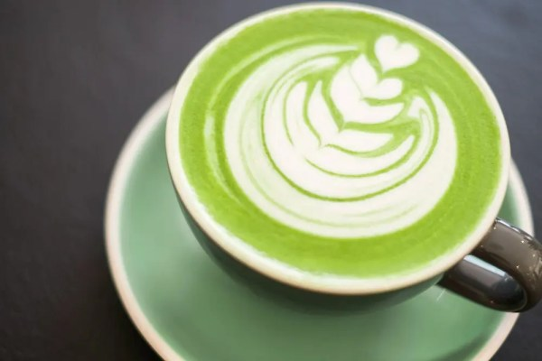 matcha latte with latte art, in a green cafe cup