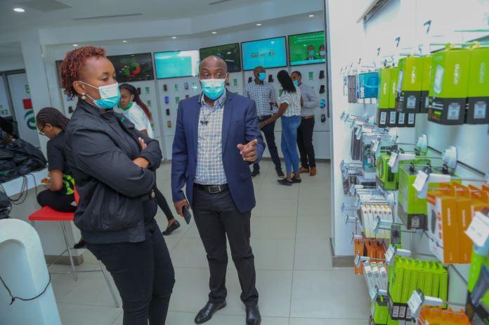 Safaricom Chief Customer Officer Sylvia Mulinge being shown the new phone accessories by Simon Kariithi - Oraimo managing director distributor to Safaricom during the launch of Safaricom newly refurbished Safaricom shop in Moi avenue, Nairobi.