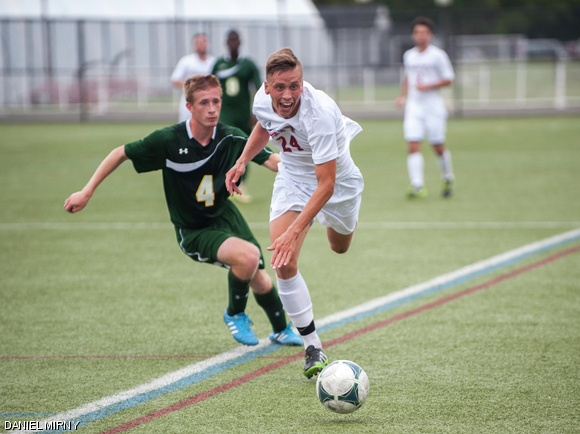 Nathaniel D. Johnson '18 races after the ball during Saturday's game against Newbury College. The game ended in a 1-1 tie after double overtime.
